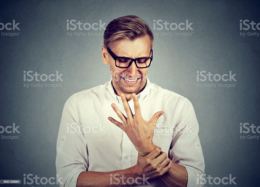 man holding painful wrist arm. Sprain pain stock photo