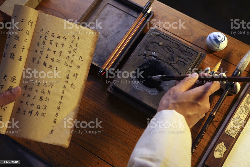 Man holding paintbrush with book stock photo