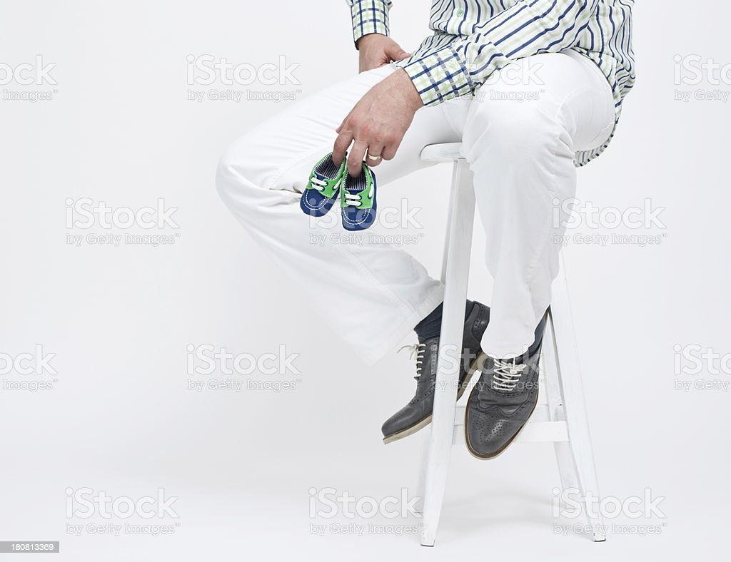 Man holding pair of baby shoes royalty-free stock photo