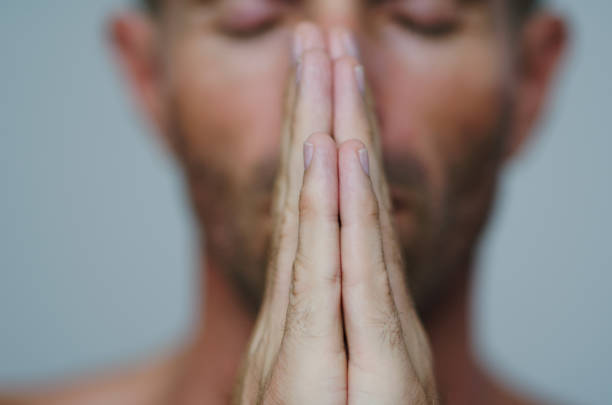 Man Holding Palms Together in Namaste Gesture Man holding palms together in a gesture of namaste, a traditional greeting in yoga prayer pose yoga stock pictures, royalty-free photos & images