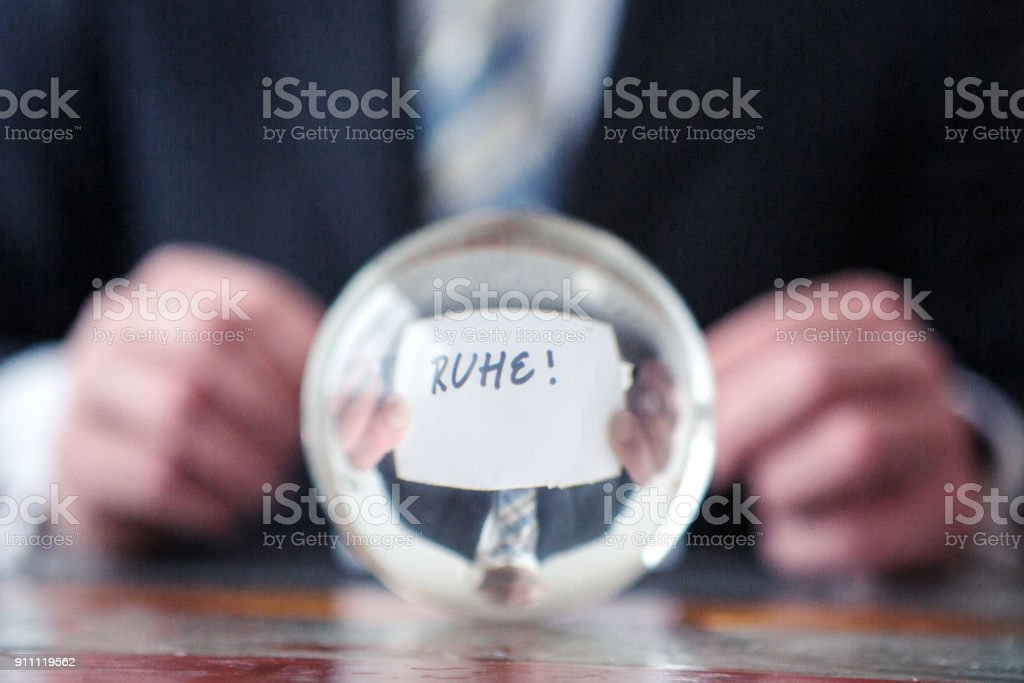 man holding paper with german word for quiet in front of glass ball stock photo