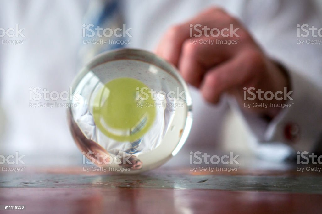 man holding paper with smiley face in front of glass ball stock photo