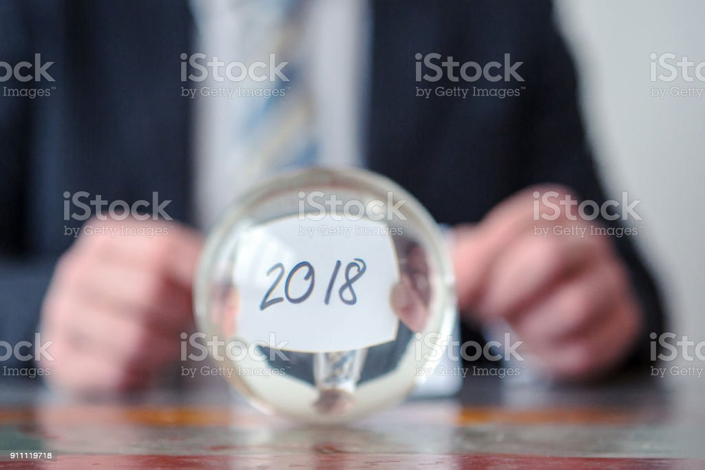 man holding paper with the numbers 2018 in front of glass ball stock photo