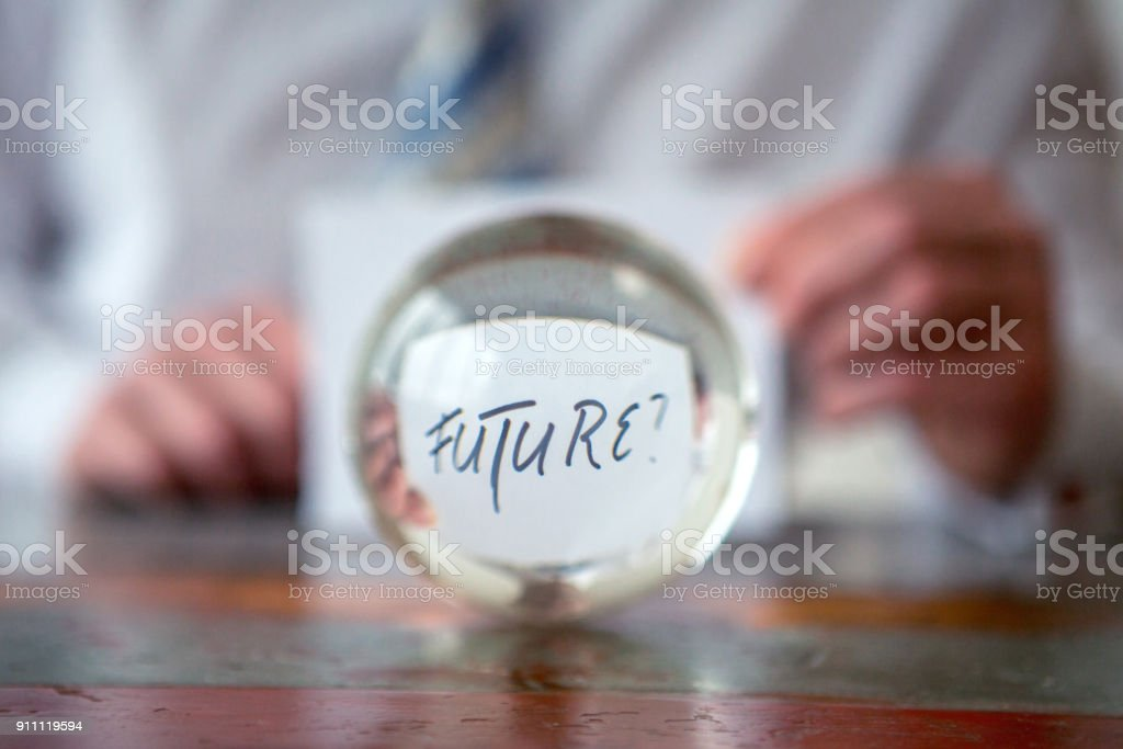 man holding paper with the word Future in front of glass ball stock photo