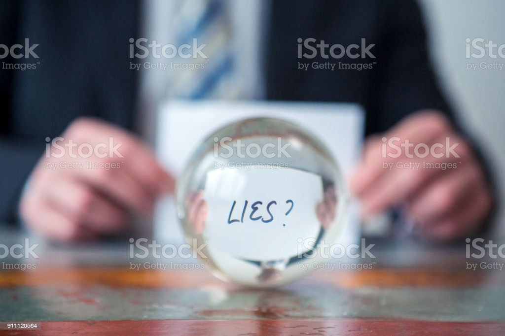 man holding paper with the word Lies in front of glass ball stock photo
