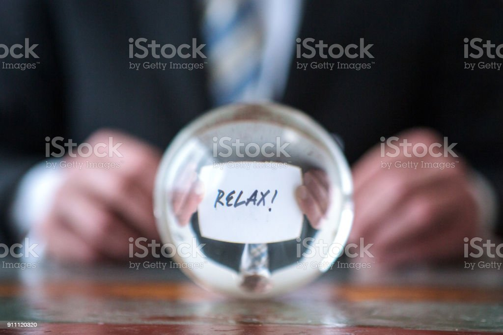 man holding paper with the word Relax in front of glass ball stock photo
