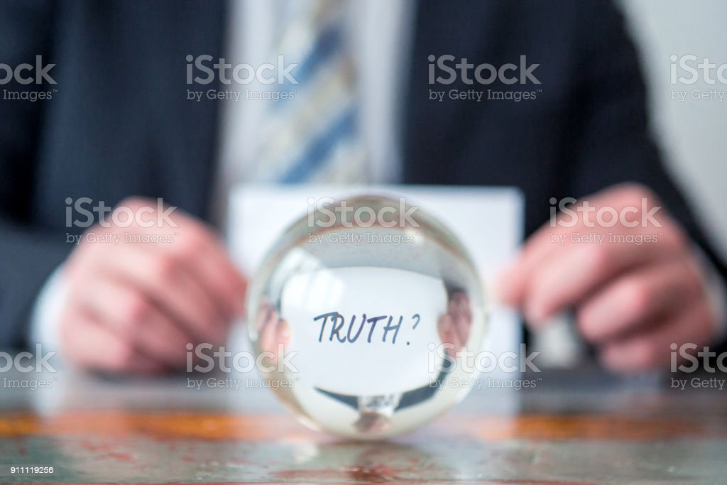 man holding paper with the word Truth in front of glass ball stock photo