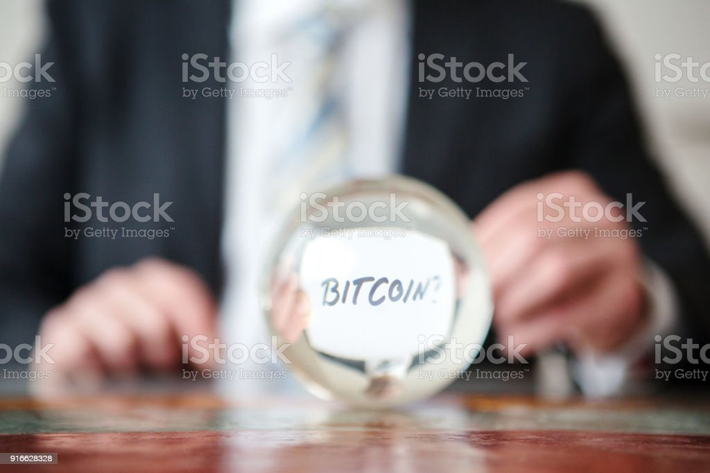 man holding paper with word Bitcoin in front of glass ball stock photo