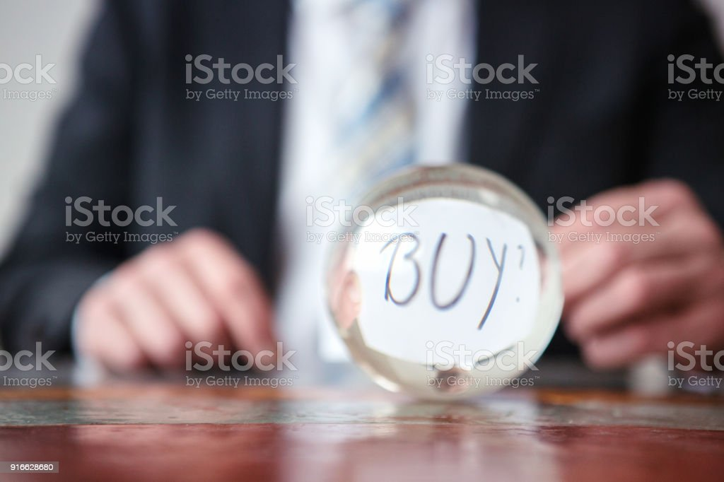 man holding paper with word Buy in front of glass ball stock photo