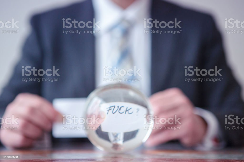 man holding paper with word Fuck in front of glass ball stock photo