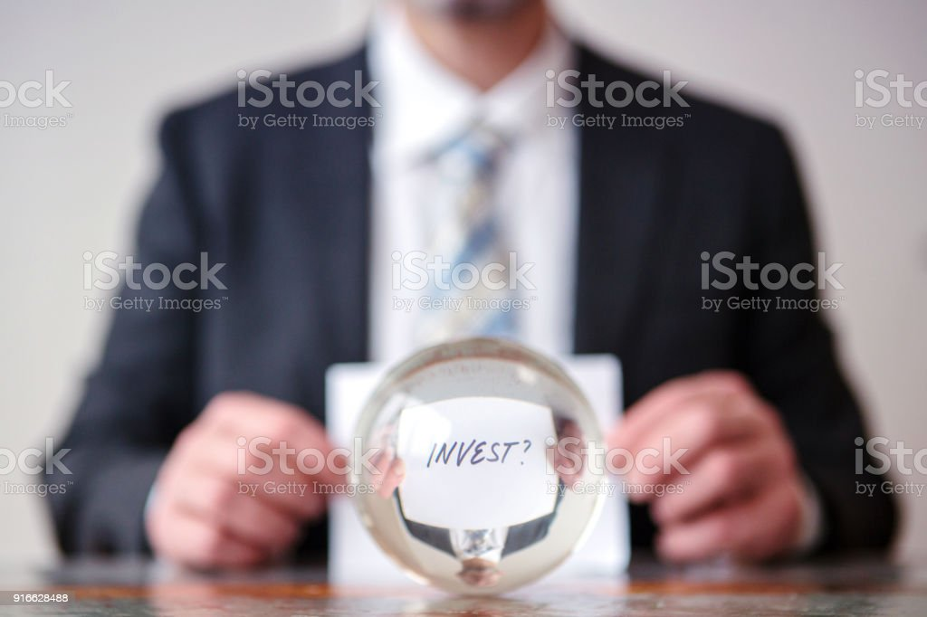man holding paper with word Invest in front of glass ball stock photo