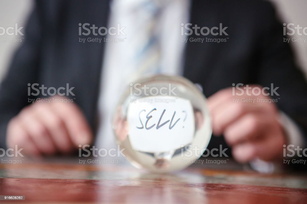 man holding paper with word Sell in front of glass ball stock photo