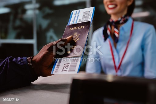 African American man holding boarding pass and passport at airline check-in desk at international airport