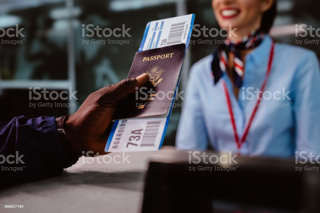 Man holding passport and boarding pass at airline check-in counter stock photo