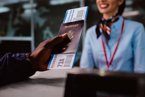 man holding passport and boarding pass at airline check-in counter - aeroplane ticket stock photos and pictures