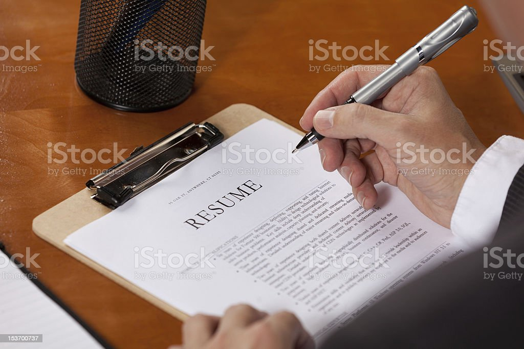 Man holding pen filling out clipboard with resume royalty-free stock photo