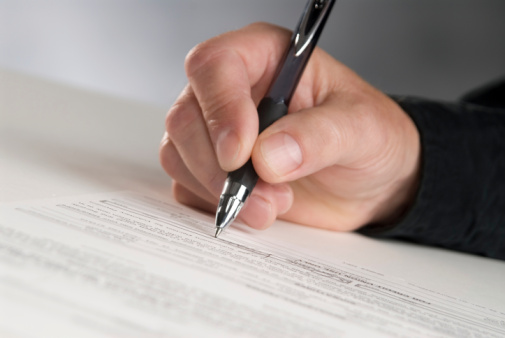 Man Holding Pen Signing Document Stock Photo - Download Image Now