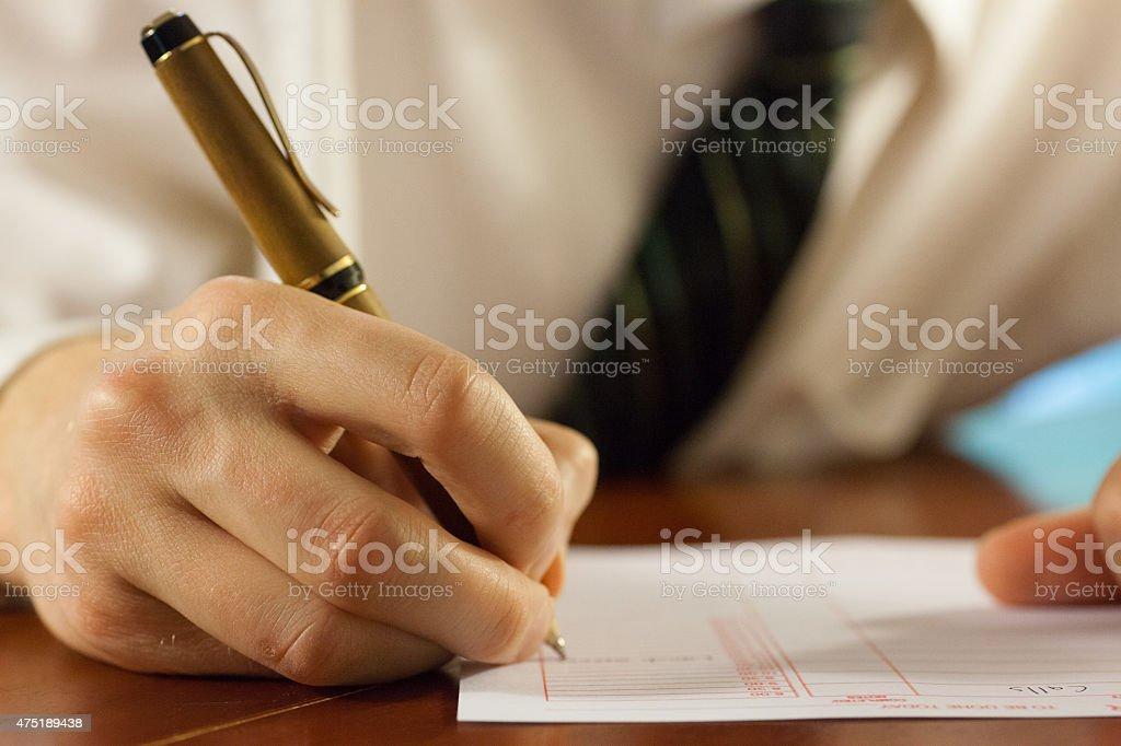 Man holding pen writing stock photo