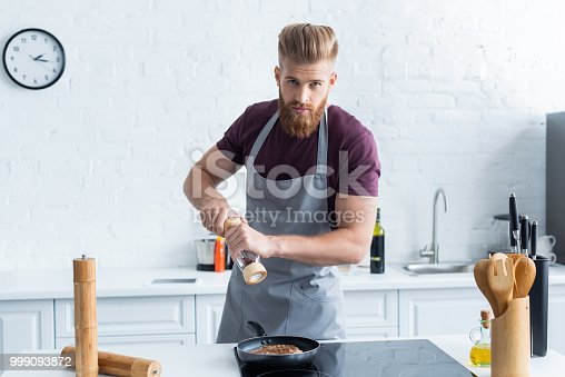 istock man holding pepper mill while cooking delicious steak and looking at camera 999093872