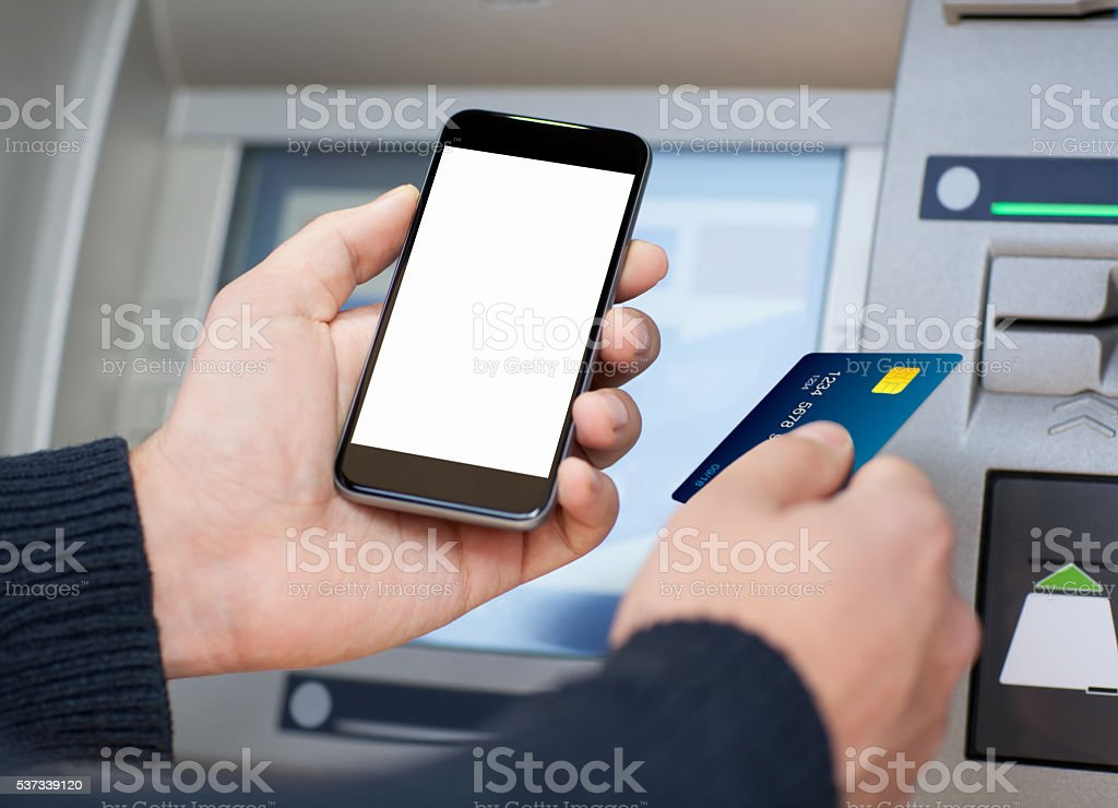 man holding phone and a credit card at an ATM stock photo