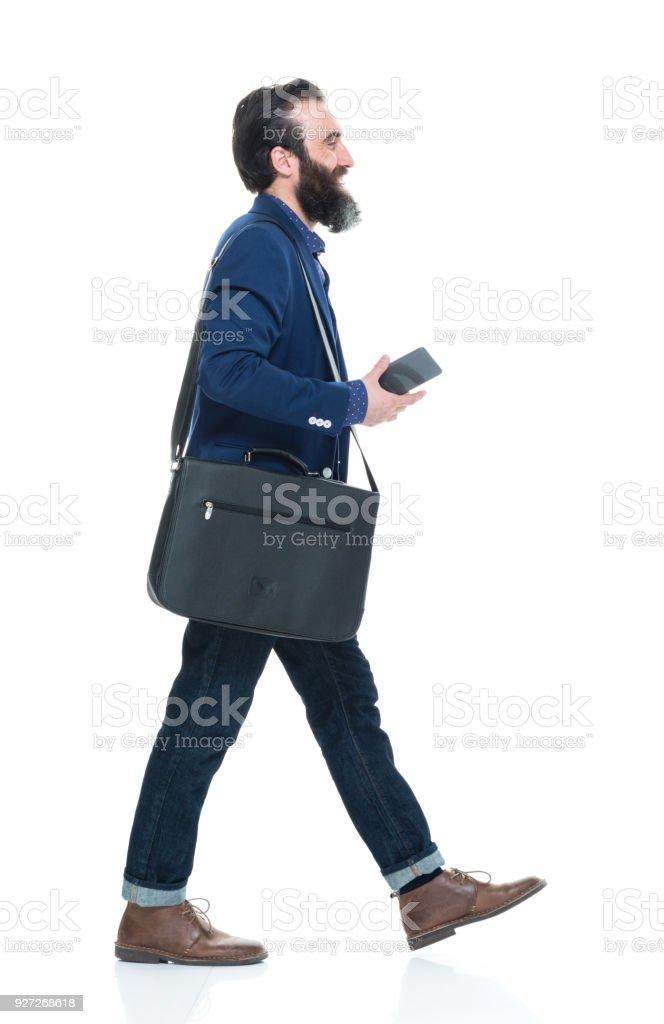 Mann hält Telefon und Dokument und zu Fuß – Foto