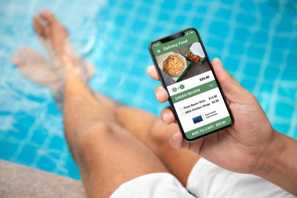 Mann mit Telefon mit app Lieferung Sushi Essen auf dem Bildschirm – Foto