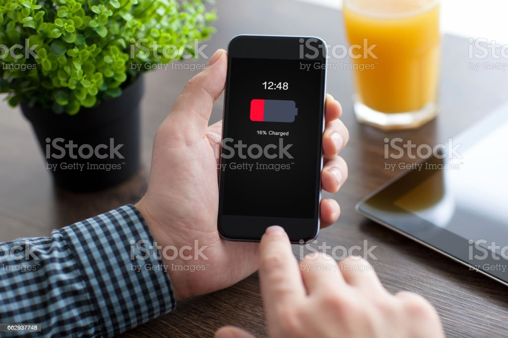 man holding phone with low charged battery on screen stock photo