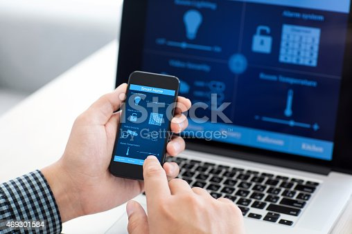 istock man holding phone with program smart home on the screen 469301584