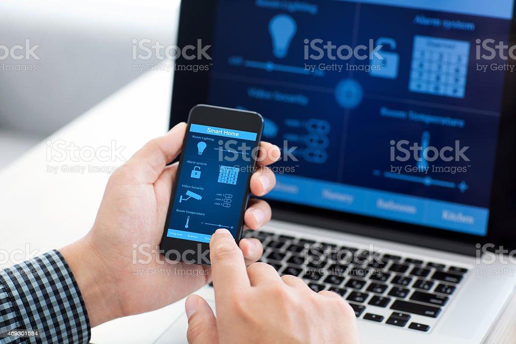 Homem segurando o telefone inteligente com o programa de casa na tela - foto de acervo