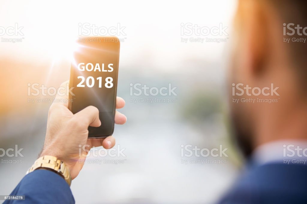 man holding phone with the words goals 2018 stock photo