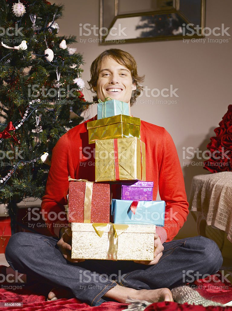 Man holding pile of Christmas gifts royalty-free stock photo