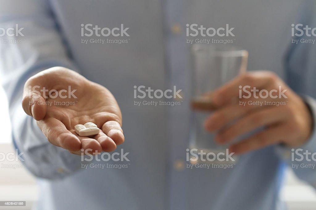 Mann holding Pillen in der einen hand und einem Glas Wasser – Foto