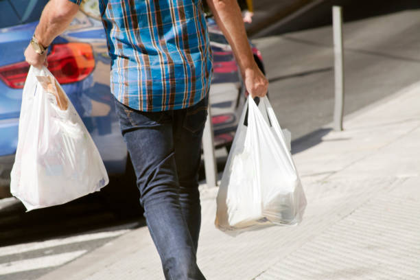 Man holding plastic bags, walking down the street. stock photo