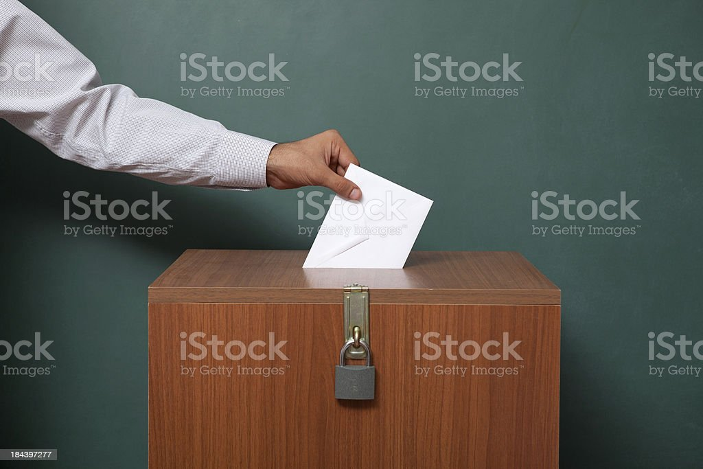 Man Holding Poll Envelope On Locked Ballot Box Voting for election in front of black blackboard Activity Stock Photo