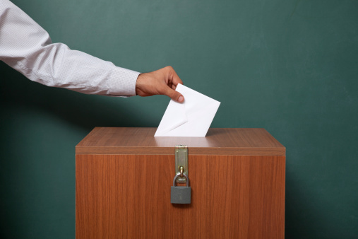 Man Holding Poll Envelope On Locked Ballot Box Stock Photo - Download Image Now