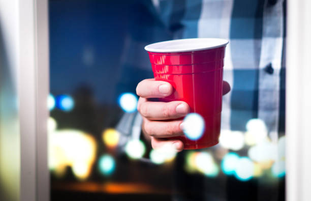 mann, der rote tasse in einer luxus oder college party hält. feier, mit spaß oder wochenende konzept. - lustige trinkspiele stock-fotos und bilder