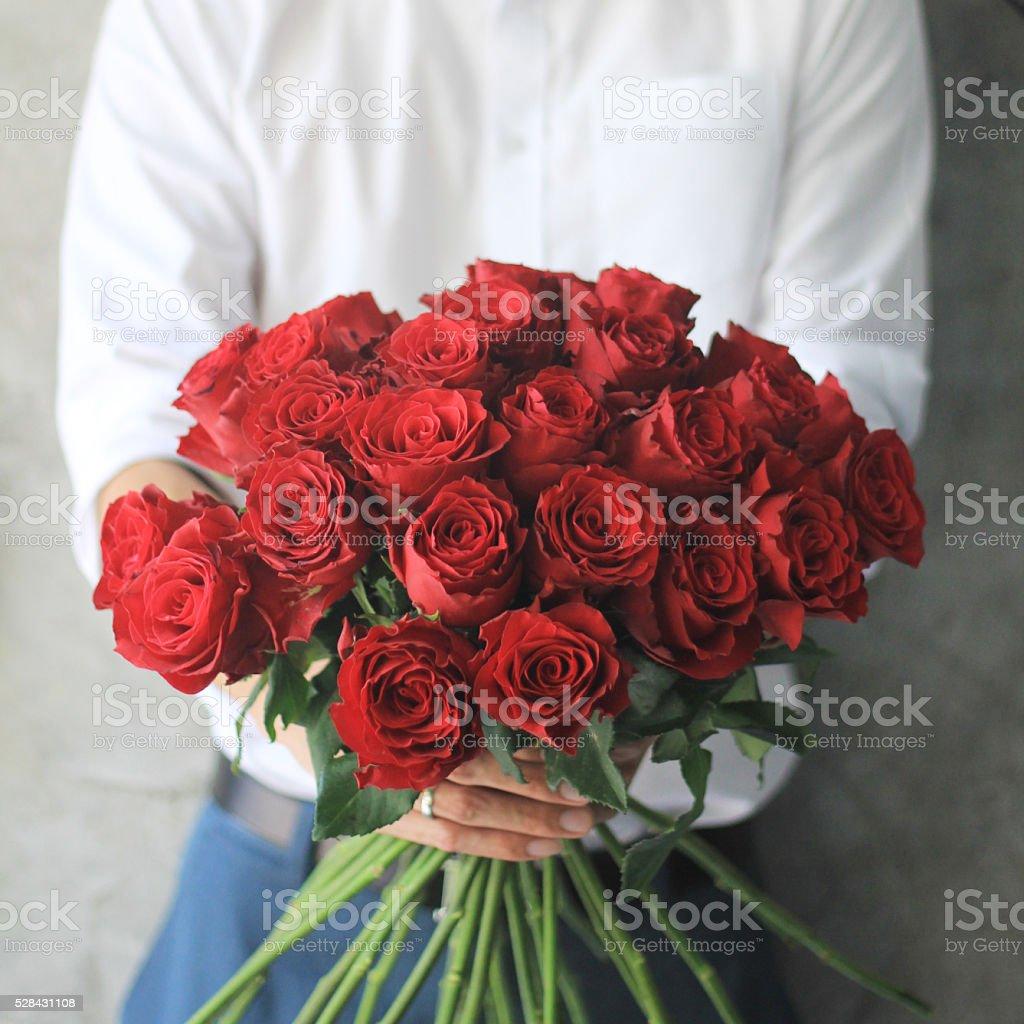 Homme tenant des roses rouges. - Photo