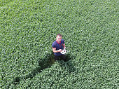 Man holding remote control quadrocopters standing in the green grass on the field.