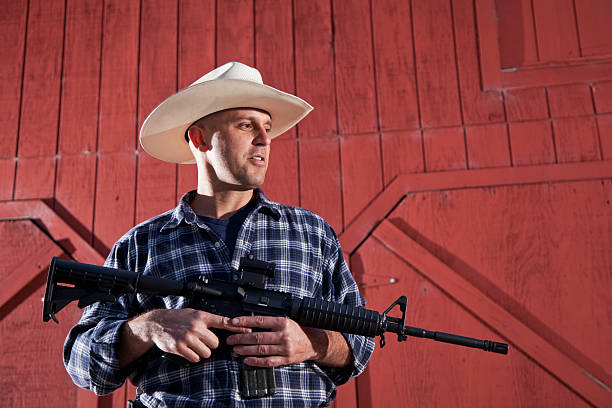 Man holding rifle Mid adult man (30s) holding AR-15 assault rifle. ar 15 stock pictures, royalty-free photos & images