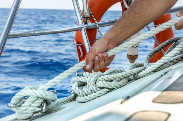 man holding rope on sailing boat - sail stock pictures, royalty-free photos & images