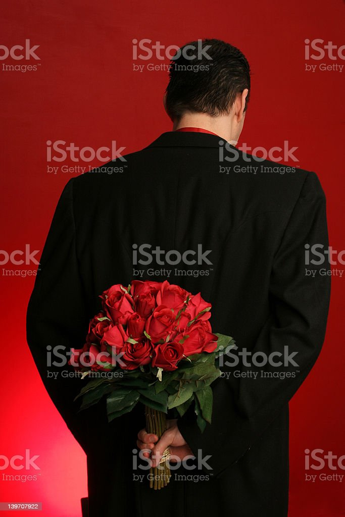 Man holding roses behind his back royalty-free stock photo