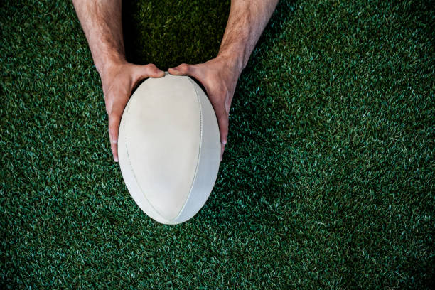 man holding rugby ball - rugby ball stock photos and pictures