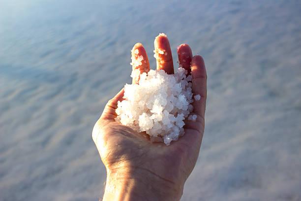 Man holding salts in salt lake in Aksaray, Turkey