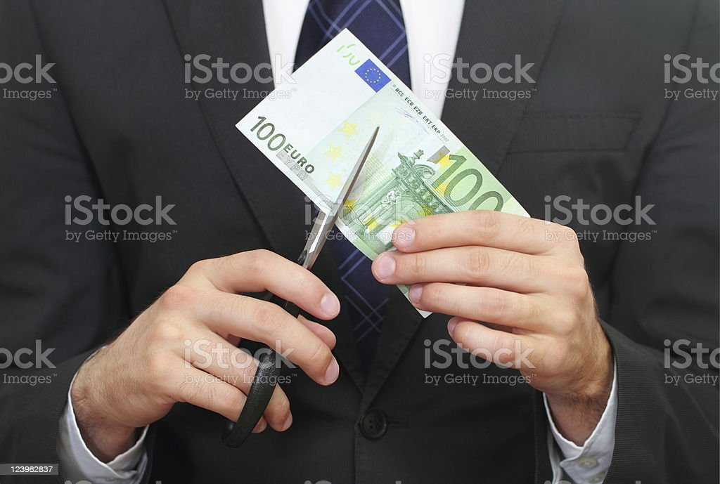 Man holding scissors cutting through a 100 Euro bill royalty-free stock photo