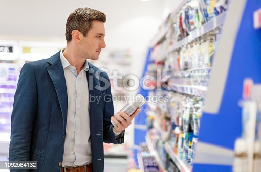 Young man holding shaving cream and looking at razors hanging on shelf in supermarket