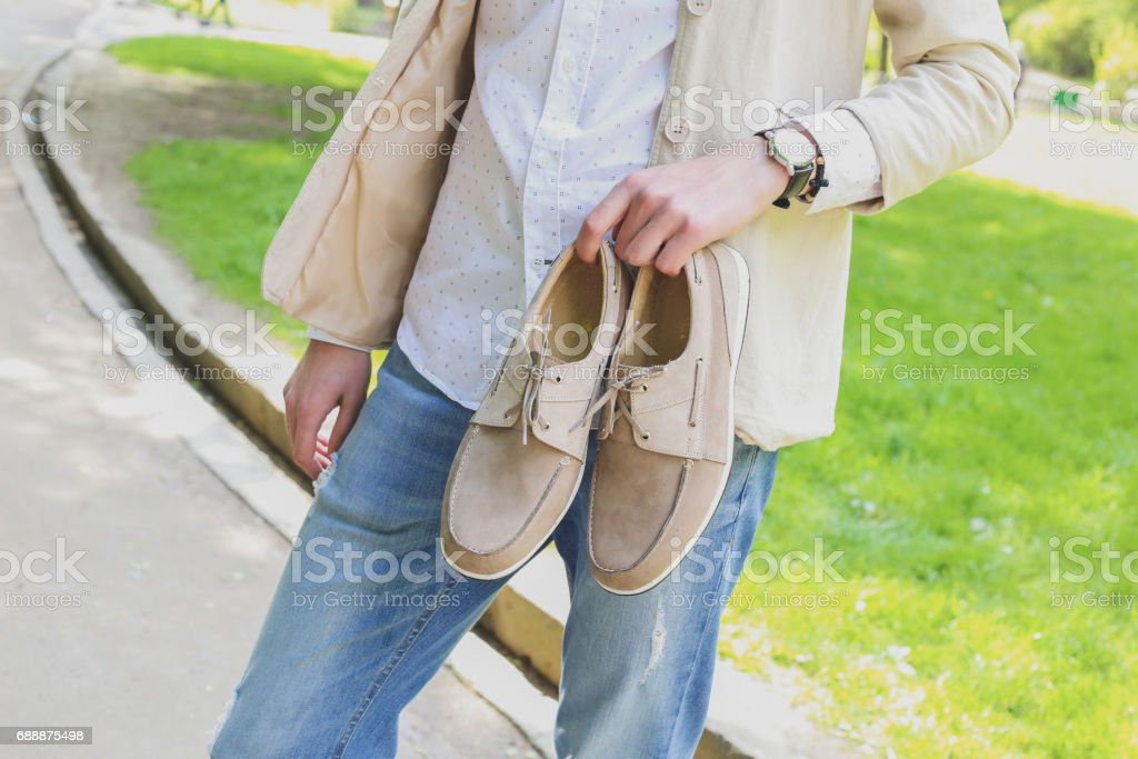 Man holding shoes. stock photo
