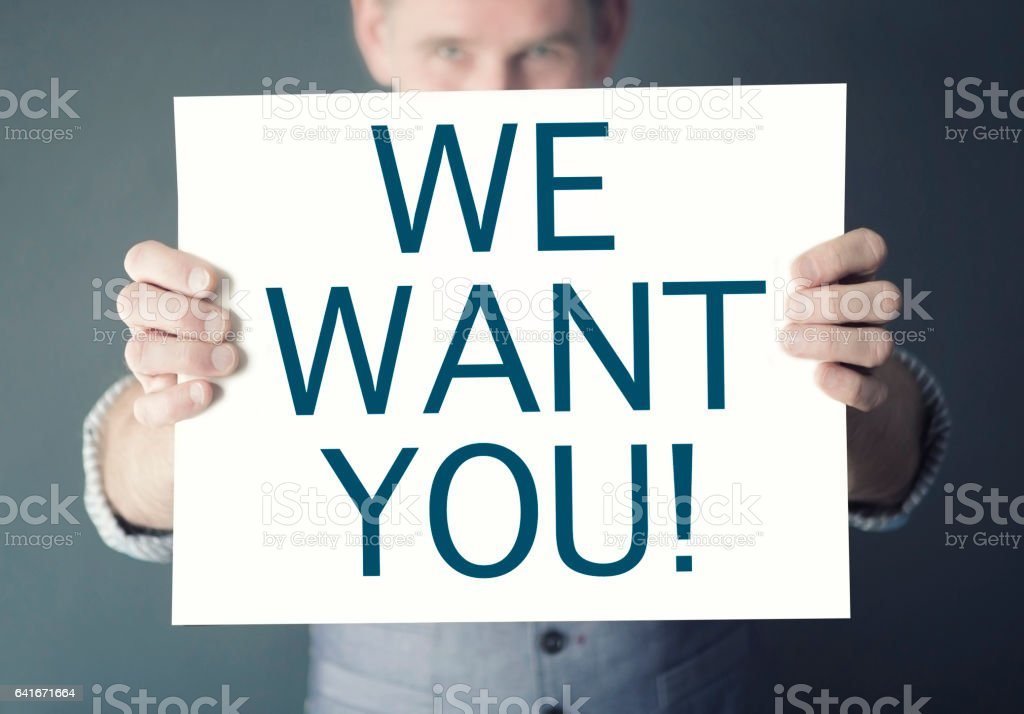man holding sign with words We Want You stock photo