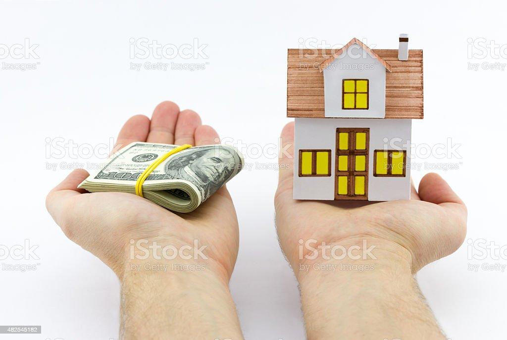 Mann hält kleine Spielzeug Haus und Stapel von Dollar – Foto
