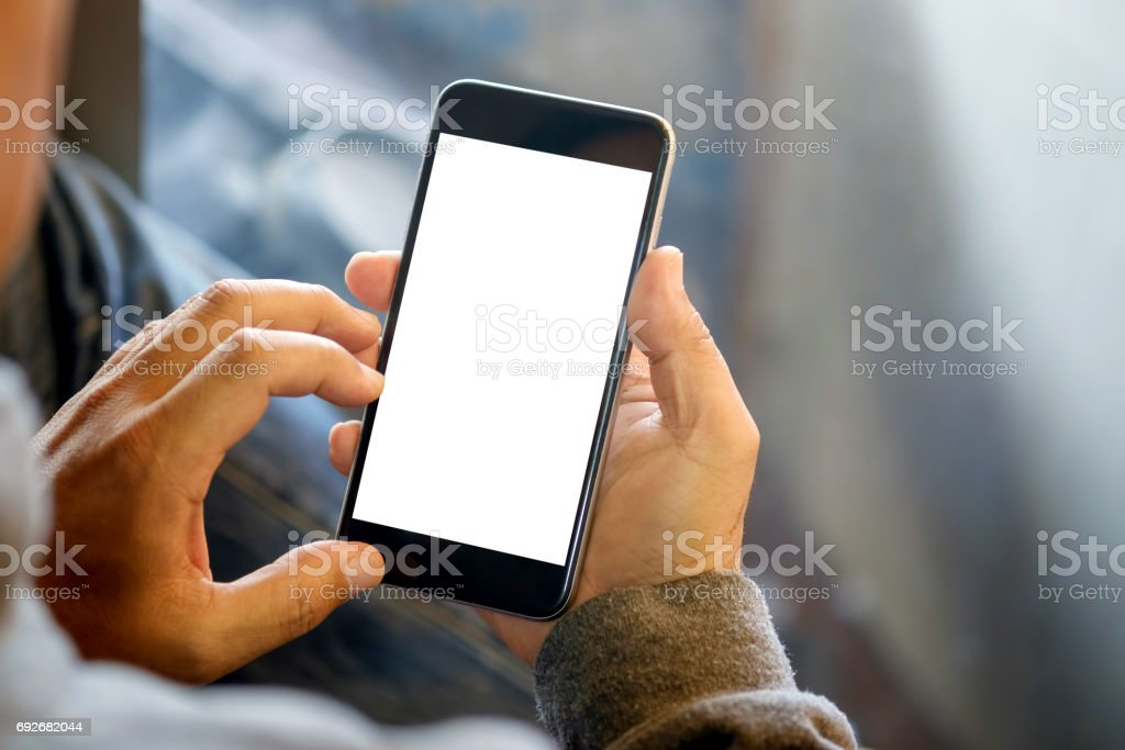 Man holding smart phone with blurred background.