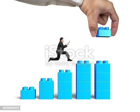 452598975 istock photo Man holding smart tablet running bar graph block hand building 509689532